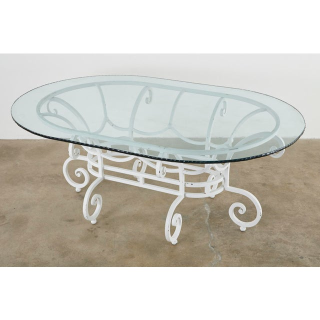 Impressive oval garden dining table featuring a large wrought iron base. Crafted from thick rods in a basket form with...