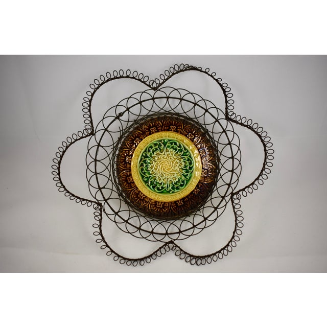 An 19th Century basket made up of a hand made twisted and looped wire holder set with a majolica plate at the center. The...