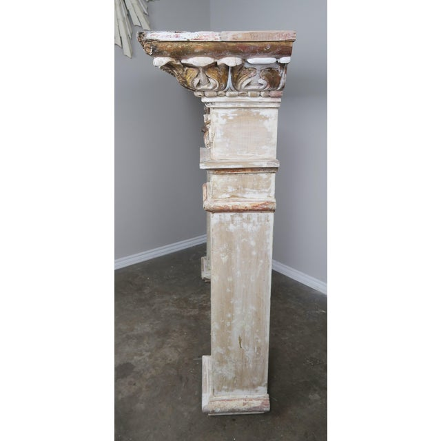 19th century Italian neoclassical style painted and parcel gilt carved wood fireplace mantel. Carved acanthus leaf detail...