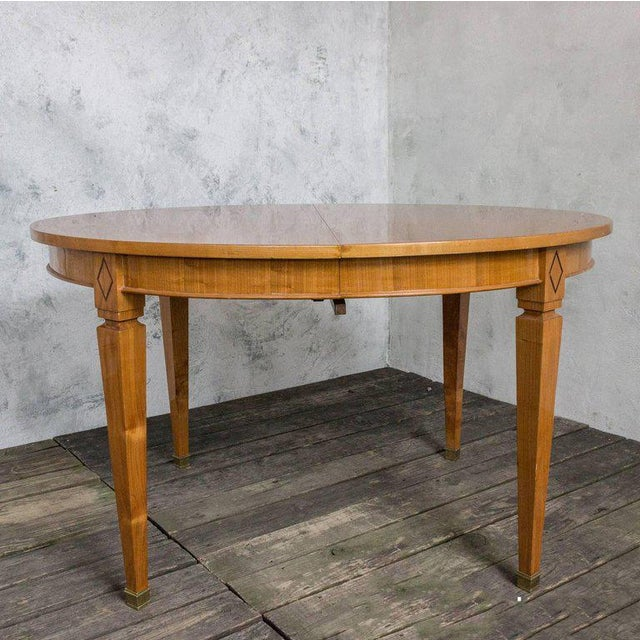 Beautiful French 1940s oval cherry dining table. It has an ebony inlay along the perimeter of the table top and a diamond...