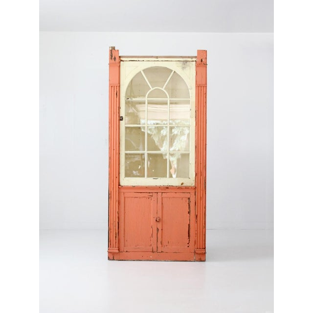 This is an antique corner china cabinet. Worn peach and cream paint this primitive cabinet. It features a bottom closed...