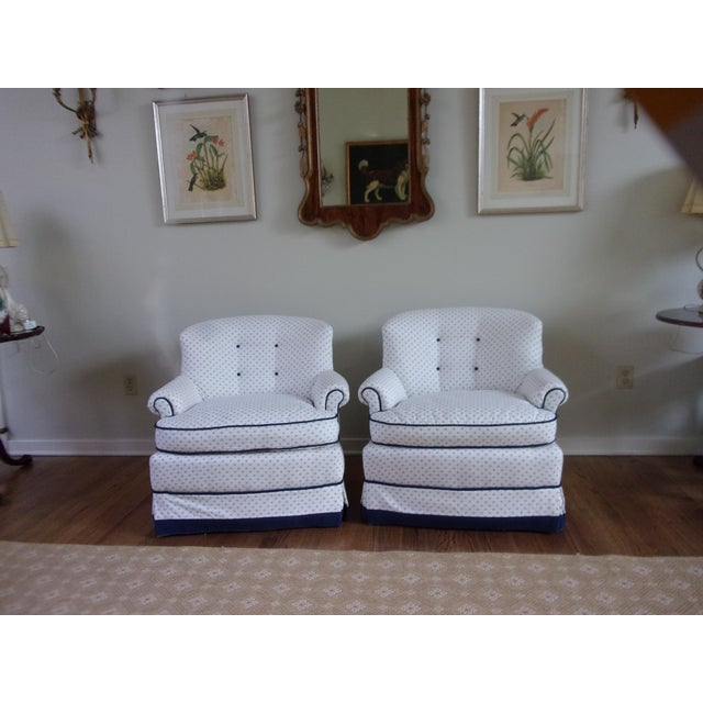 A pair of swivel tub chairs freshly upholstered in a neutral white and blue fabric with navy banding and cording. Legs are...
