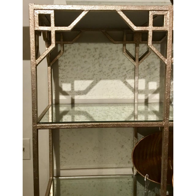 Stylish modern Currey & Co. Breslin Étagère finished in a textured silvery taupe, geometric detail, four antiqued mirror...