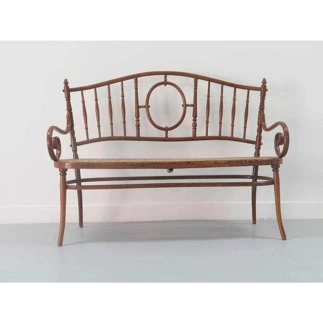 Beautiful bentwood and caned settee in the style of Thonet. Simple and classic design with fantastic original wood finish....