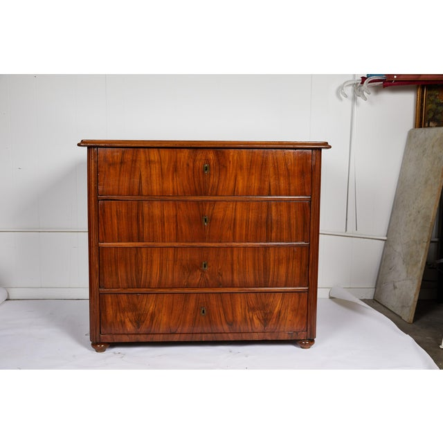 19th century large scaled and sleek Continental Biedermeier commode with a burl bookplate rosewood veneer on three sides....