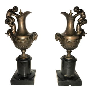 Pair of 19th C. Urns on Marble Stands Bearing Cherubs & Rams Heads For Sale