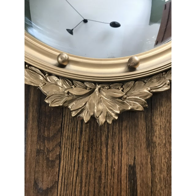 Beautiful vintage convex mirror. Frame is constructed of wood and finished with gold paint. Eagle motif at top with...