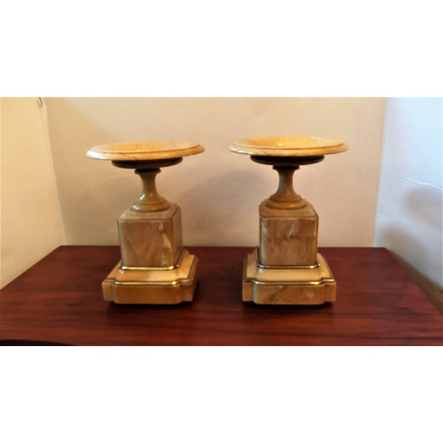 A pair of neoclassic sienna marble tazzas with burnished bronze mounts. The dish top with bronze center resting on a...