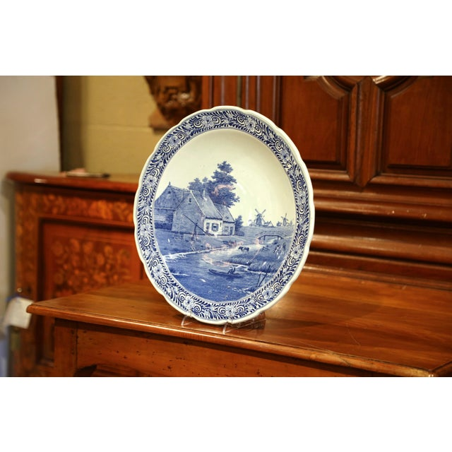 This large antique platter was crafted in Holland, circa 1920; the large wall hanging plate depicts a pastoral scene in...
