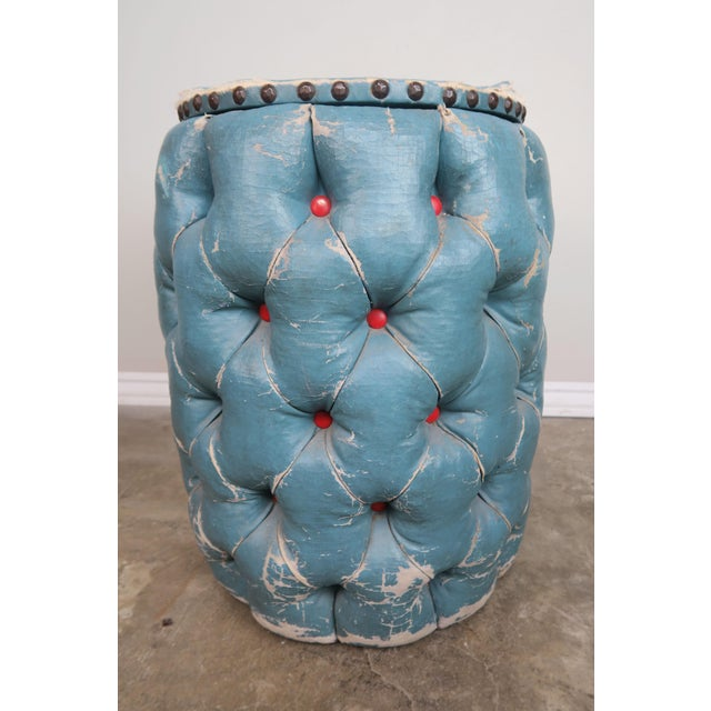 Blue Tufted Stool with red tufts. There is a lid that opens up to a storage area detailed with nailheads.
