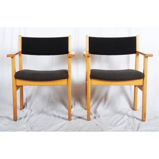 These Danish armchairs designed by Hans J. Wegner are made of solid oak and covered with original fabric, and were...