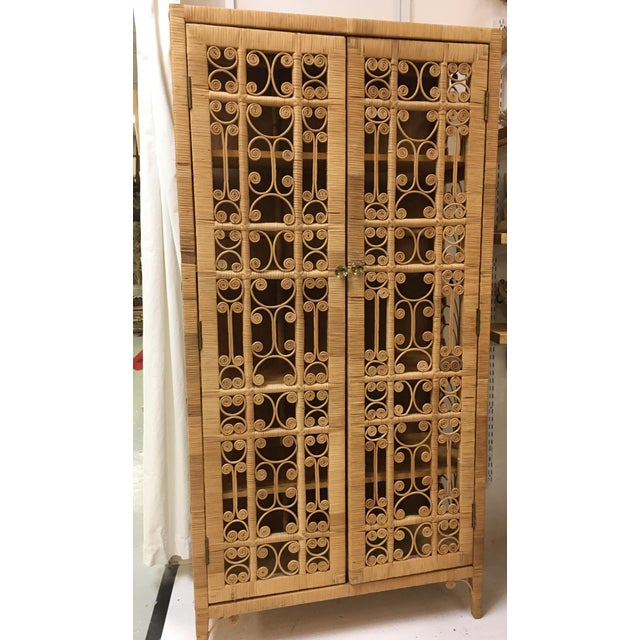 Unique vintage rattan cabinet. Cabinet features two doors and five shelves. This piece is sturdy and well made. Please see...