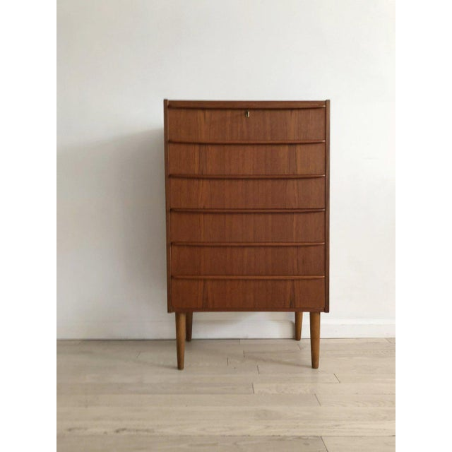 Timeless, classic teak chest of drawers. Imported from Denmark, made in the 1950s. Bookmatched drawers. Lock and key for...