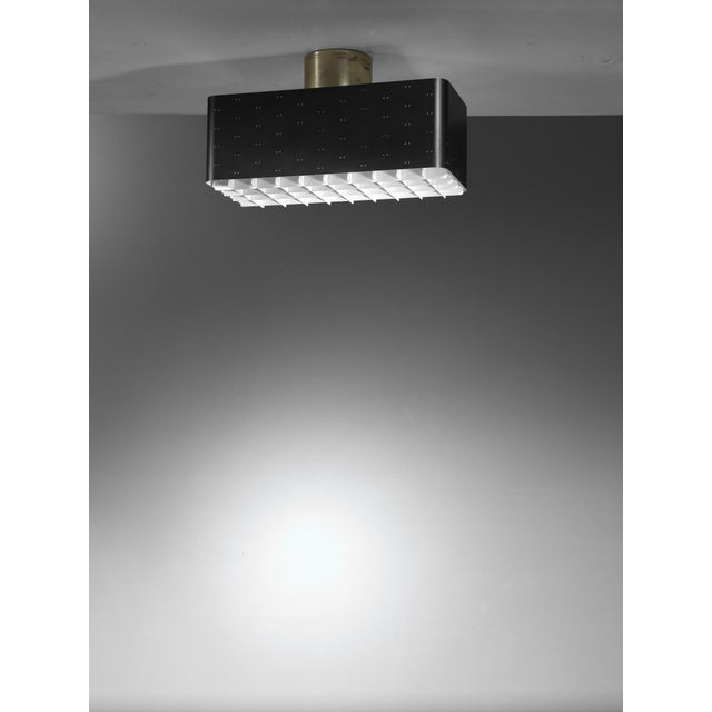 A rectangular ceiling lamp by Paavo Tynell for Idman, made of black lacquered brass with pinhole perforations. The lamp...