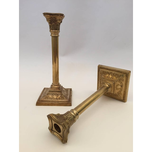 A very nice pair of George III neoclassical brass candlesticks with square bases and columnar shafts supporting urn form...