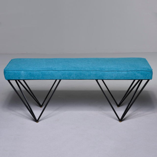 Italian mid-century style bench has black enameled metal base with open triangular form legs and brass feet. Upholstered...