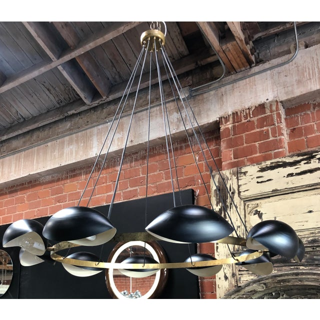 Large round 1960s chandelier: a brass wheel with 8 lights black lacquered bulbs is hanging down from the ceiling, because...