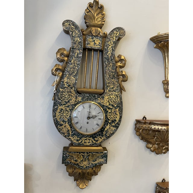 English wall clock made in London. Hand carved with gilt wood frame in lyre with Lucite and eglomise decoration. With key.