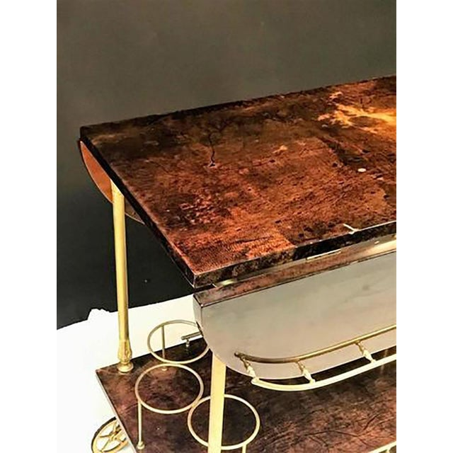 Beautiful chocolate toned goatskin Aldo Tura bar cart with gilded brass handles, hardware and wheels. Opens up to extend...