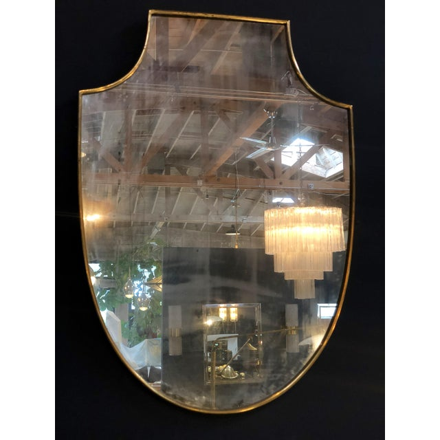 Elegant brass framed Italian mirror in a shield design with a needed border, Italy, 1960s.