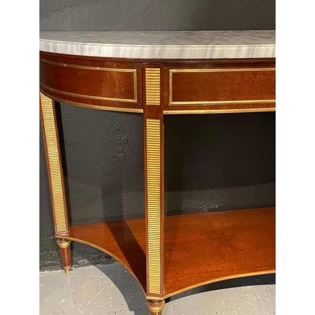 Russian neoclassical demilune marble top console, sideboard or sofa table having a tortoiseshell Veneer Finish. This...