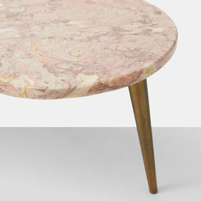 A biomorphic, amoeba shaped coffee table with rose tone marble and tapered brass legs.