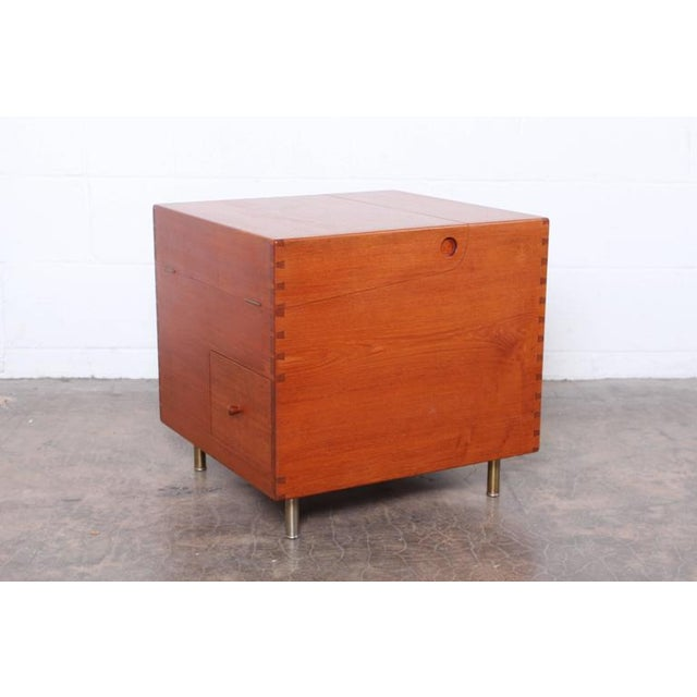 A solid teak cube bar cabinet model 8034 designed by Hans Wegner for Andreas Tuck, with dovetail joinery, on satin chromed...