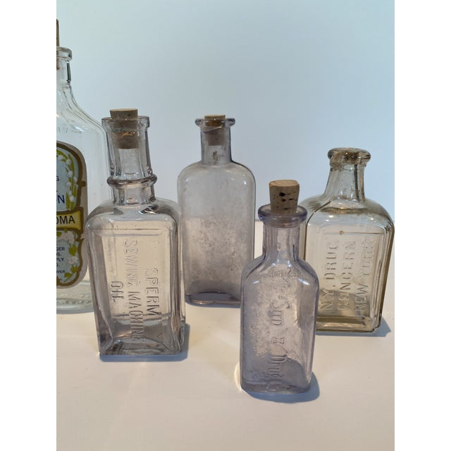 Vintage Glass Apothecary Bottles - Set of Seven. They all have a faint lavender tint to them. Variety of sizes and shapes,...