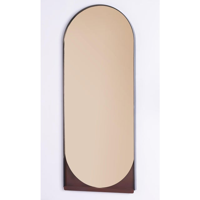 Simplicity is key to the Slip Mirror, whose thin blackened stainless steel frame delicately holds an oblong mirror. A...