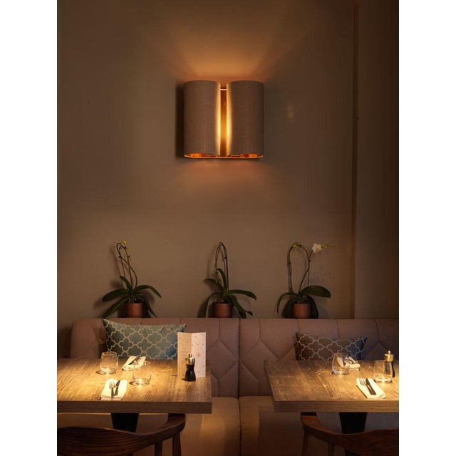 A steel metal work wall light with natural shade which creates a striking light effect up and down the wall plus reflected...