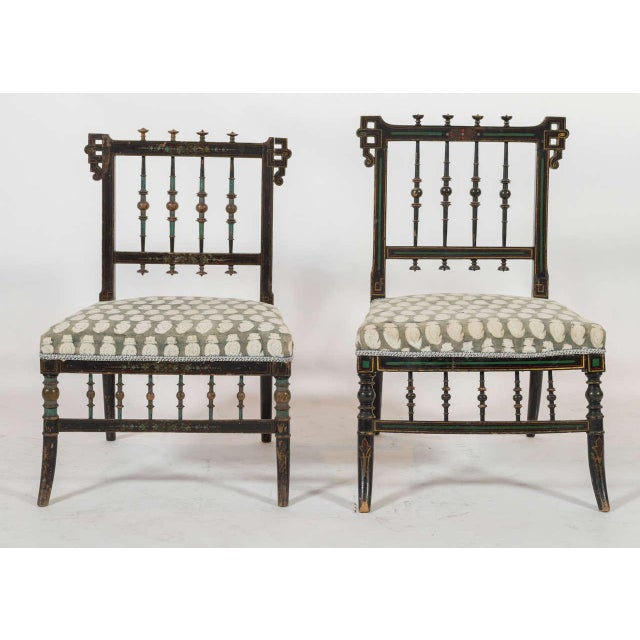 Pair of two small parlor chairs with patterned upholstery. Both chairs are similar, but one is slightly smaller than the...
