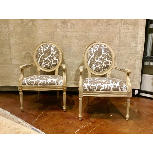 Pair of Classic French style Avery arm chair with an antiqued cream frame, rossett medallions, and fluted legs, stylish...