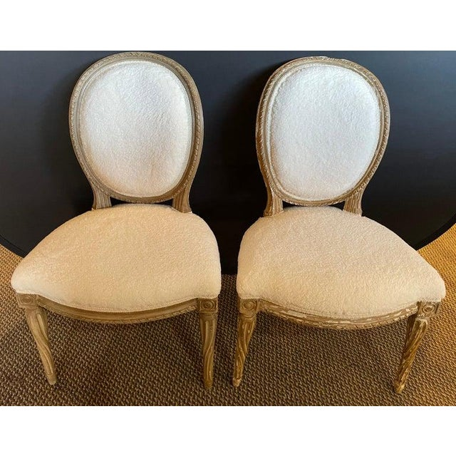 Pair of Jansen distressed Sherpa upholstered side chairs. Each having a cameo back on a distressed from worn and beaten in...