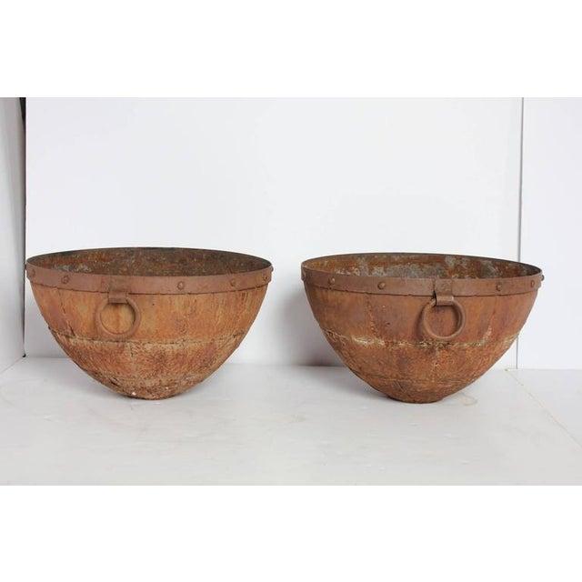 Large antique iron bowls.
