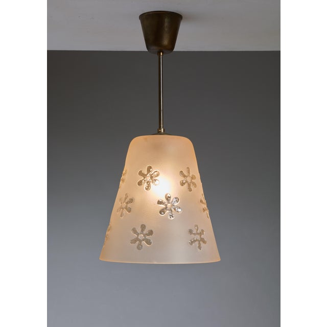 A Swedish pendant made of a cone shaped, frosted light orange glass shade. The glass has a beautiful relief decoration...