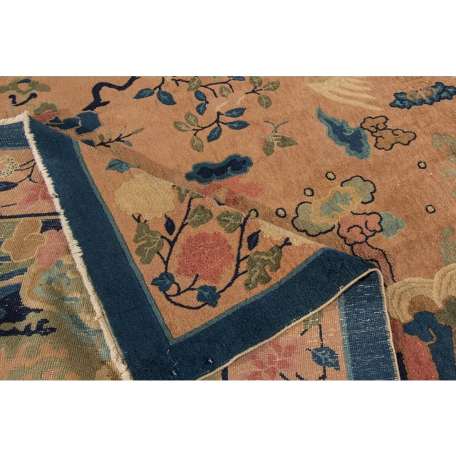 A beautiful hand-knotted antique Chinese deco wool rug with a peach field and multi-color accents in all-over Chinese...