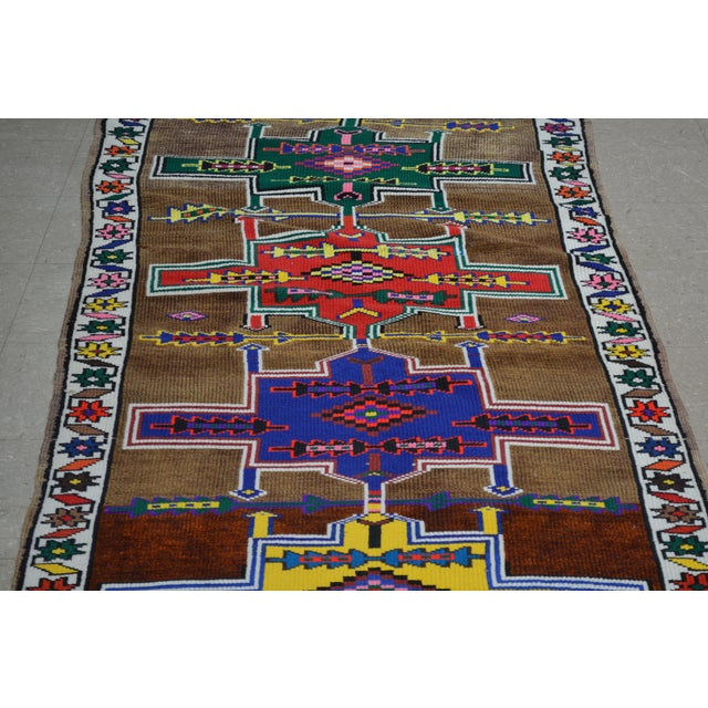 Vintage Kurdish hand knotted runner rug with natural colors and geometric pattern.