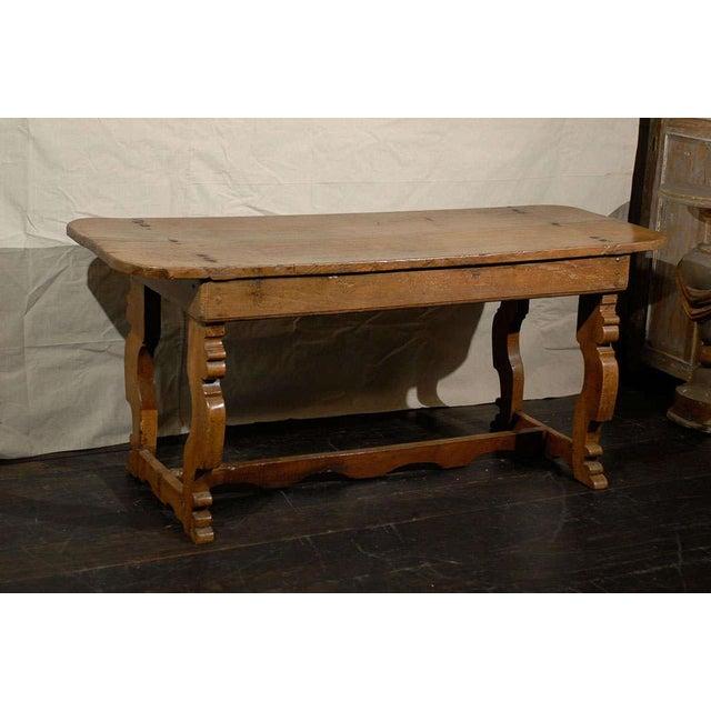 An 18th century Italian trestle base farm table. This Italian chestnut wood farm table features a single plank top,...