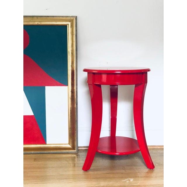 Sleek pair of juicy red lacquered end tables. Round top supported by 3 flared legs and one shelf underneath.