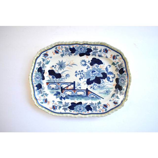 An antique mid-19th-century oblong serving plate or small platter, with a chinoiserie transferware design of a bridge and...
