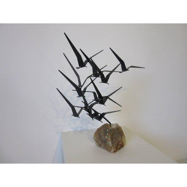 A welded metal flock of birds sculpture mounted on a natural quartz type stone with shades of brown tones, the birds are...