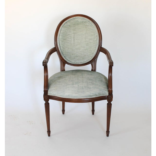 Upholstered oval-back Fauteuil with floral rosettes on fluted legs. Some wear to wood and fabric. No makers mark. Seat,...