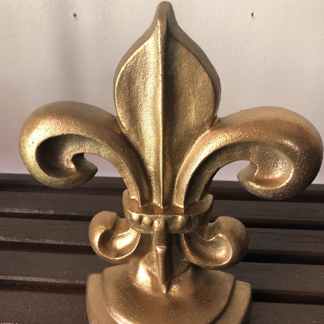Beautiful pair of Fleur De Lis pair of gilded iron bookends, perfect for the interior designer.
