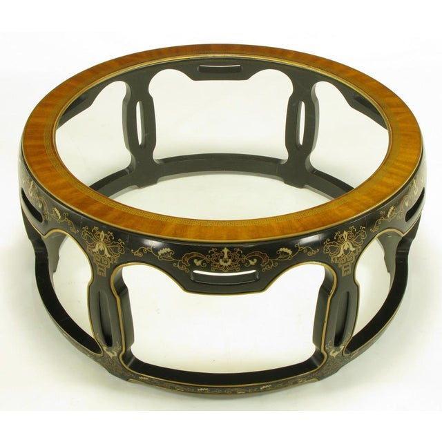 Caved and dark chocolate lacquered wood, open drum form, coffee table. Hand painted gilt and ivory floral details. Ribbon...