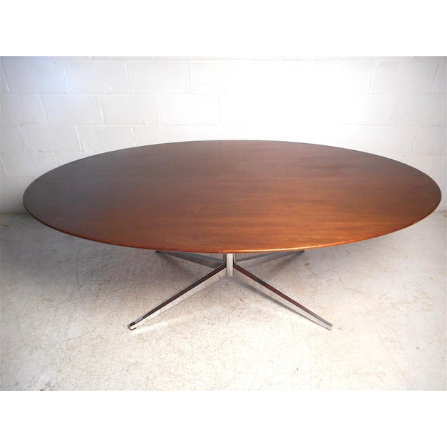 Impressive midcentury dining table by Knoll International. Large wooden tabletop supported by a sturdy chrome base. An...