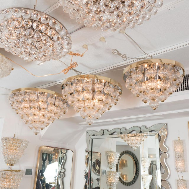 Chrome and brass flush mount fixture with fluted, suspended glass balls arranged in tiers. 10 candelabra sockets