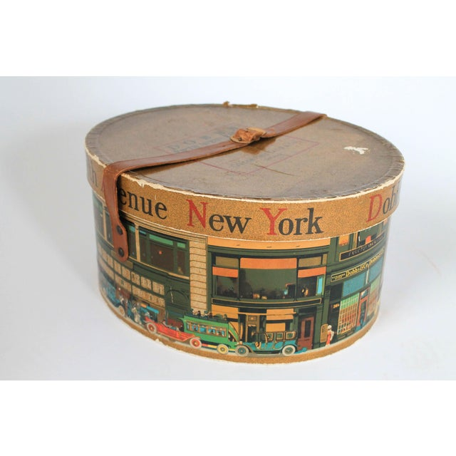 Vintage Dobbs Fifth Avenue New York hat box with a leather buckle closure depicting a city scene. Overall age wear.