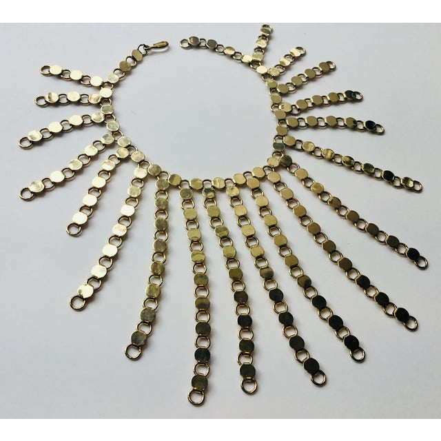 Striking gold tone sunburst necklace, circa 1990s. Interlocking gold links, loop clasp. Due to the unique nature of the...