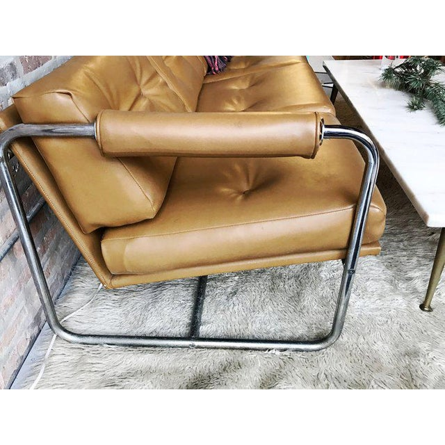 "A chrome & naugahyde sofa. Seat Height: 18"" Arm Height: 25"""