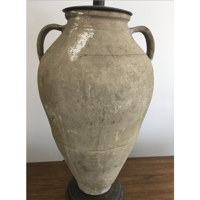 Oversized clay lamp with a distressed finish. This large jug shape lamp has a beautiful textured, aged finish. The top is...
